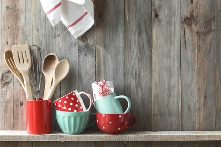 47181133 - kitchen cooking utensils in ceramic storage pot on a shelf on a rustic wooden wall, space for text
